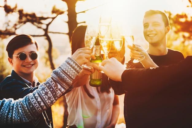 Grupo de jovens animados, sorrindo e tilintando taças de álcool enquanto comemoram em uma paisagem maravilhosa