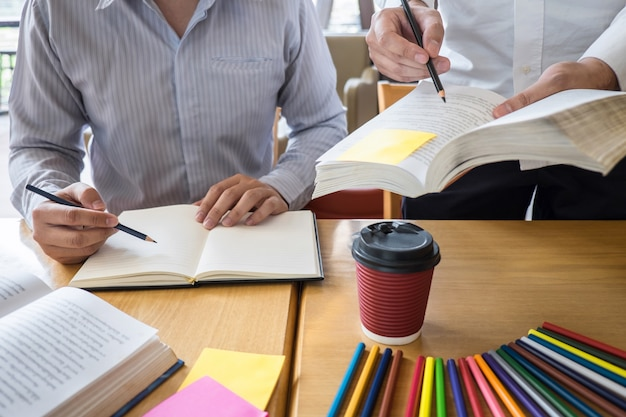 Grupo de jovens aprendendo a estudar nova lição ao conhecimento na biblioteca durante o ensino de educação de amigos a se preparar para o exame, conceito de adolescentes de amizade de campus de juventude