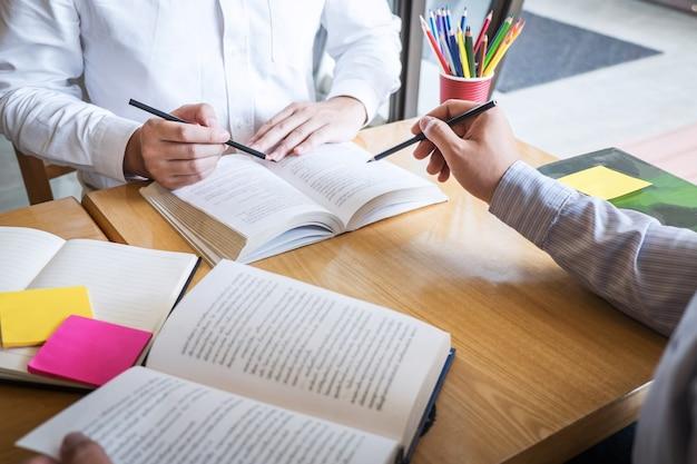 Grupo de jovens aprendendo a estudar nova lição para o conhecimento na biblioteca durante o ensino da educação de amigos na preparação para o exame