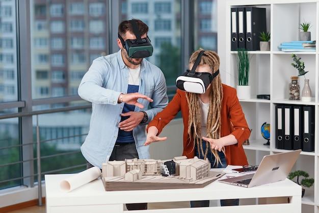 Grupo de jovens arquitetos em óculos de realidade virtual trabalhando com a maquete de uma casa em um escritório moderno