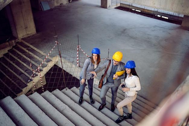 Grupo de jovens arquitetos inovadores bem sucedidos subindo as escadas e falando sobre o objeto. edifício no interior do processo de construção.