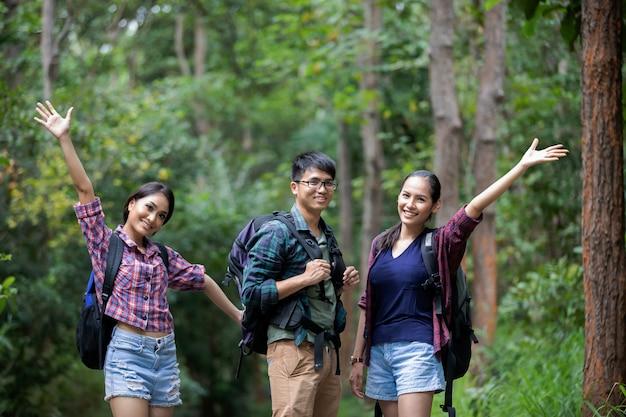 Grupo de jovens asiáticos caminhando com mochilas de amigos e posando na floresta