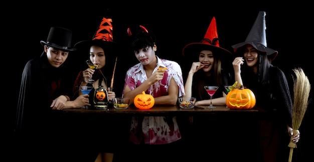 Grupo de jovens asiáticos em traje comemora festa de halloween em fundo preto com conceito para o festival de moda de halloween. gangue de adolescentes asiáticos em cosplay halloween. fantasma fantasma, mal do grupo adolescente tailandês.