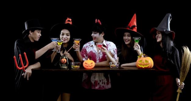 Grupo de jovens asiáticos fantasiados comemora festa de halloween na parede preta com conceito para o festival de moda de halloween. gangue de adolescentes asiáticos em cosplay halloween. fantasma fantasma, mal do grupo adolescente tailandês.