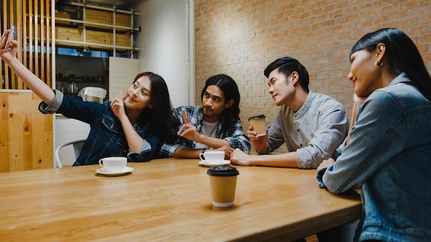 Grupo de jovens asiáticos felizes, se divertindo muito e fazendo selfie com a amiga enquanto estão sentados juntos no café-restaurante.