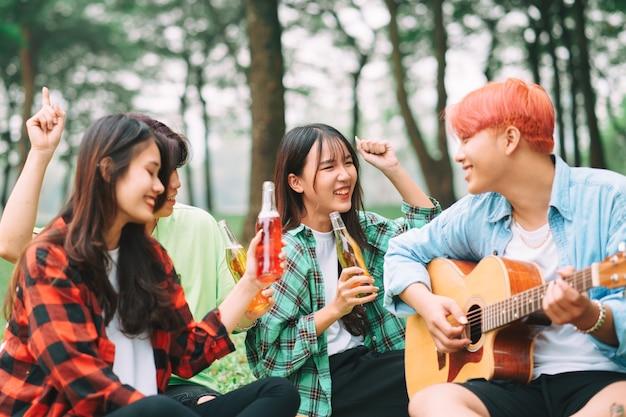 Grupo de jovens asiáticos felizes sentados ao violão e cantando no parque