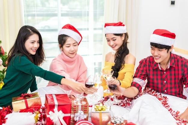 Grupo de jovens asiáticos que comemoram festa do ano novo em casa com copos de vinho