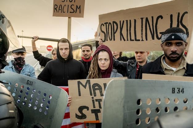 Grupo de jovens ativistas multiétnicos sérios em pé com placas na rua e protestando juntos, os guardas os parando com escudos