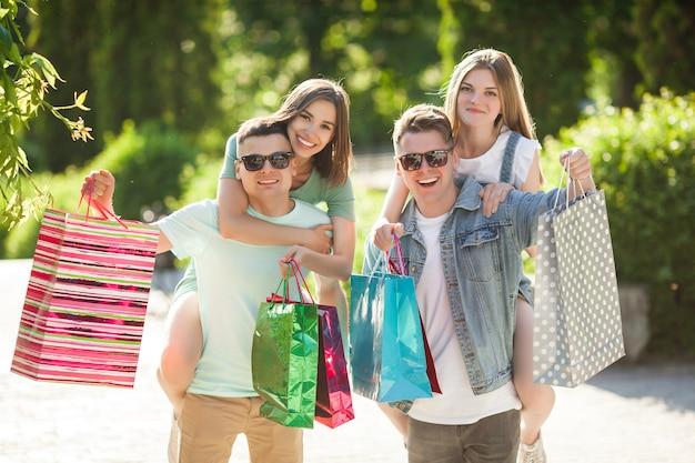 Grupo de jovens atraentes fazendo compras. amigos ao ar livre segurando sacolas de compras e sorrindo. amigos alegres juntos.