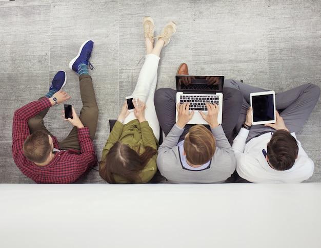 Grupo de jovens atraentes, sentado no chão usando um laptop, tablet pc, telefones inteligentes, sorrindo.
