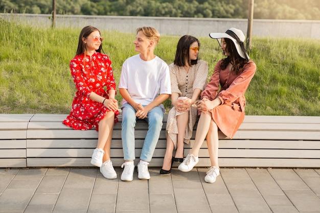 Grupo de jovens bonitos sentados no parque conversando