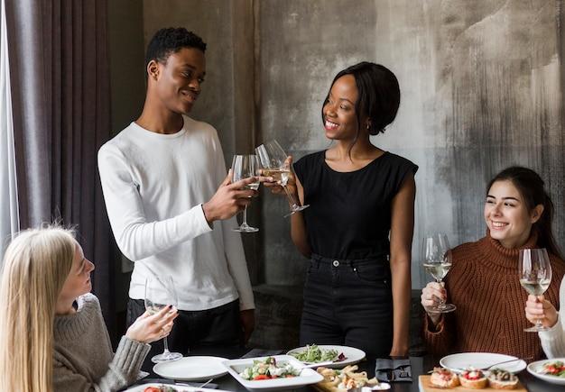 Grupo de jovens brindando com taças de vinho