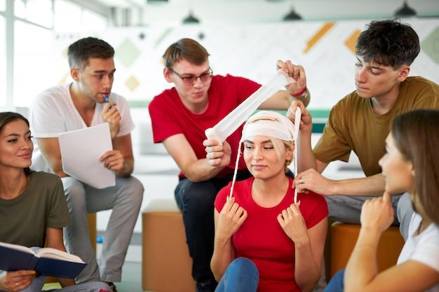 Grupo de jovens caucasianos aprendendo como garantir uma vida sentados juntos na aula