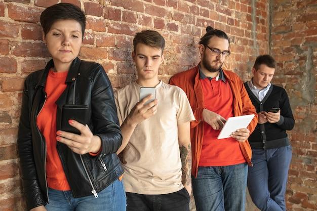 Grupo de jovens caucasianos felizes em pé atrás da parede de tijolos. compartilhando notícias, fotos ou vídeos de smartphones ou tablets, jogando e se divertindo. redes sociais, tecnologias modernas.