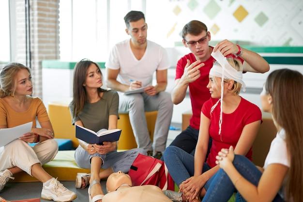 Grupo de jovens caucasianos pratica o tratamento de um paciente com curativos, o conceito de primeiros socorros. dentro de casa