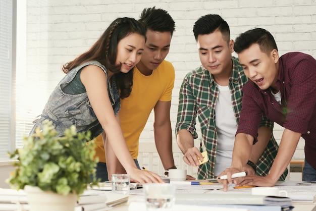 Grupo de jovens colegas asiáticos em pé ao redor da mesa e olhando para algo