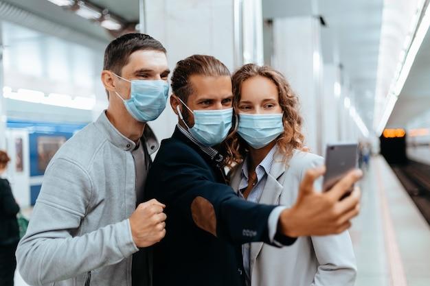 Grupo de jovens com máscaras protetoras tirando selfies no metrô