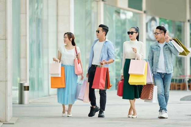 Grupo de jovens com óculos de sol andando na rua com butiques e sacolas de compras nas mãos