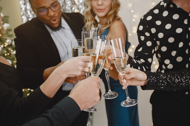 Grupo de jovens comemorando o ano novo. amigos bebem champanhe.