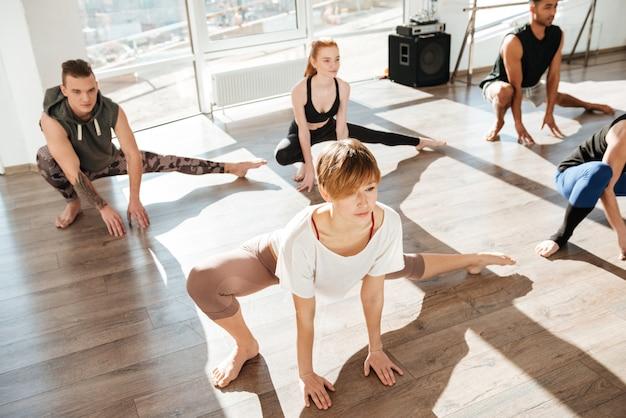Grupo de jovens concentrados, esticando e praticando ioga