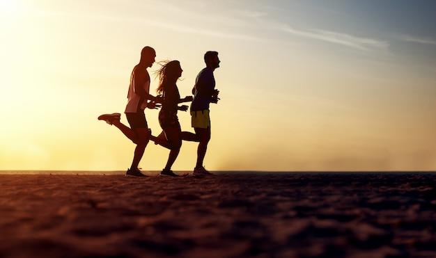 Grupo de jovens correndo na praia por do sol lindo de verão.