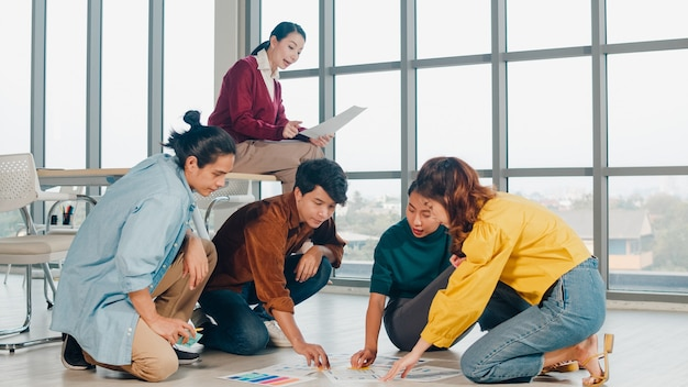 Grupo de jovens criativos da ásia em roupas casuais, discutindo o brainstorm de negócios, reunião de idéias, plano de projeto de design de software de aplicativo móvel estabelecido no chão do escritório. conceito de trabalho em equipe do colega de trabalho.