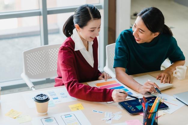 Grupo de jovens criativos da ásia, supervisor do chefe feminino japonês, estagiário de ensino ou nova funcionária hispânica, ajudando com difícil atribuição no escritório moderno. conceito de trabalho em equipe do colega de trabalho.