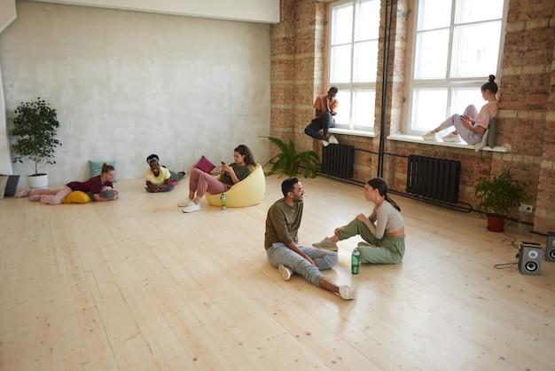 Grupo de jovens dançarinos relaxando após o treinamento esportivo, ouvindo música e usando telefones celulares no estúdio de dança