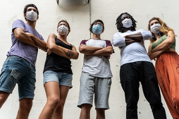 Grupo de jovens de diferentes etnias, com uma máscara no rosto e braços cruzados
