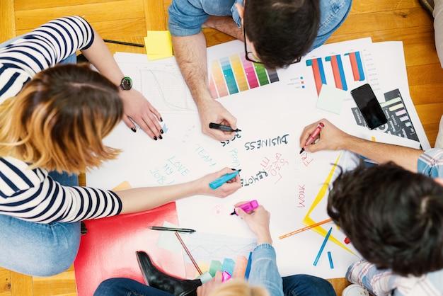 Grupo de jovens designers modernos, sentado no chão e fazendo novos planos.