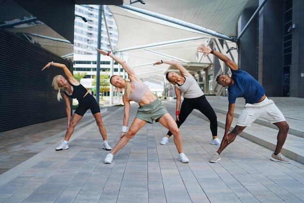 Grupo de jovens e idosos fazendo exercício ao ar livre na cidade.