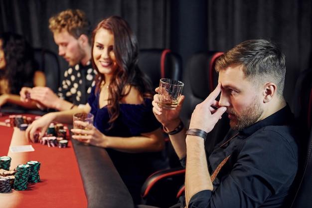Grupo de jovens elegantes que jogando pôquer no cassino juntos