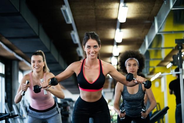 Grupo de jovens em forma na academia se exercitando