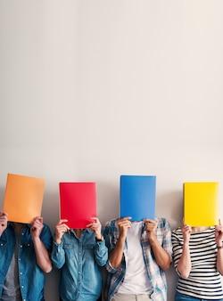 Grupo de jovens em pé e encostados na parede, segurando pastas coloridas na frente de suas cabeças.