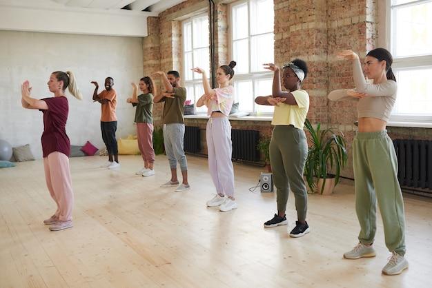 Grupo de jovens em pé e repetindo os movimentos do instrutor na aula de ginástica