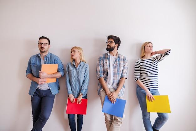 Grupo de jovens em pé na fila com pastas nas mãos. expressão facial séria, na parede do branco do fundo. arranque o conceito do negócio.