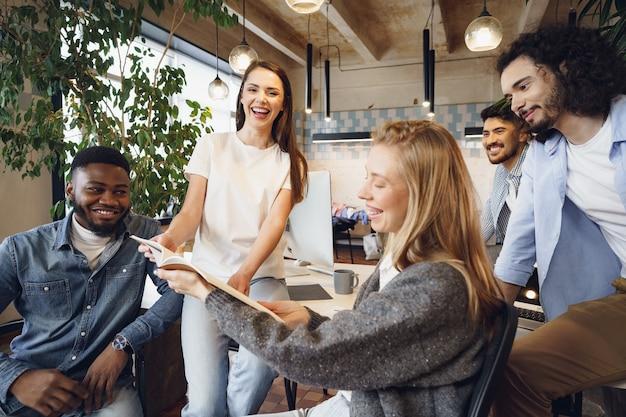Grupo de jovens empresários discutindo documentos durante reunião no escritório