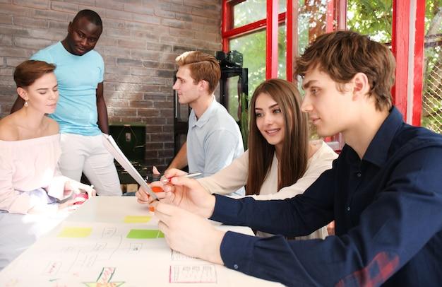 Grupo de jovens empresários e designers. eles estão trabalhando em um novo projeto. conceito de inicialização.