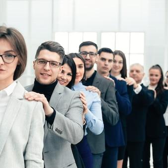 Grupo de jovens empresários em pé atrás uns dos outros. o conceito de trabalho em equipe