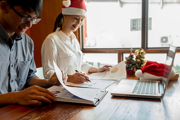 Grupo de jovens empresários estão comemorando no local de trabalho com chapéus de papai noel