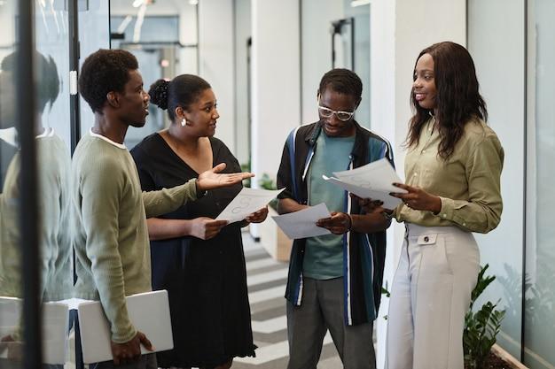 Grupo de jovens empresários negros de pé no corredor do escritório moderno e discutindo gráficos e ...