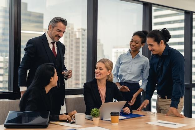 Grupo de jovens empresários trabalhando e se comunicando sentados à mesa do escritório
