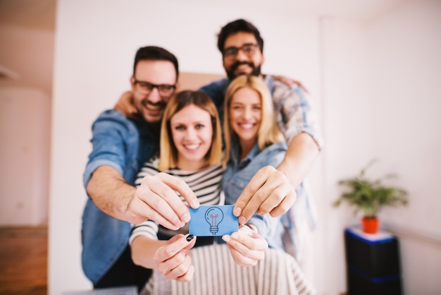 Grupo de jovens encantadores felizes segurando juntos um pequeno papel azul com uma lâmpada para idéias criativas e inovadoras