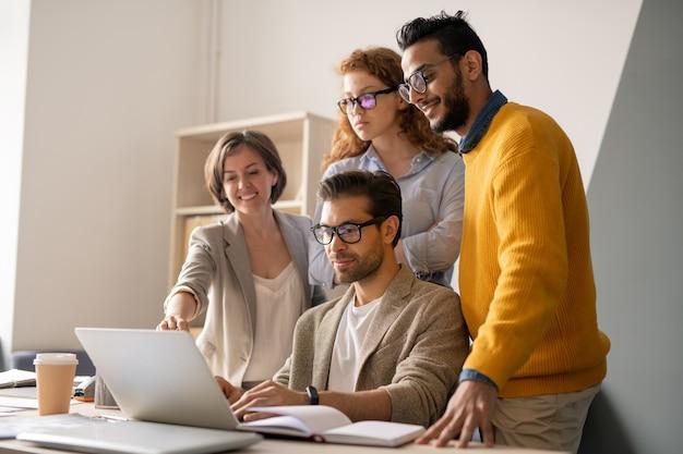 Grupo de jovens especialistas em negócios multiétnicos olhando para a tela do laptop e analisando a apresentação juntos no escritório