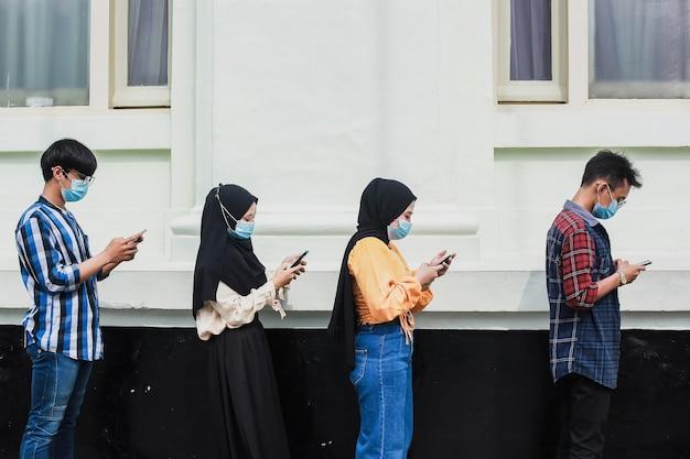 Grupo de jovens esperando para entrar no mercado de uma loja, enquanto mantêm distância social em linha durante o período do vírus corona
