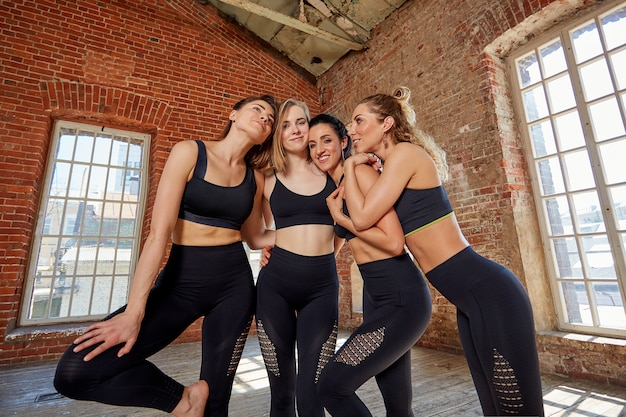 Grupo de jovens esportes meninas descansando depois de um treino em um estúdio espaçoso. amizade feminina no ginásio, relaxante após fitness, dentro de casa, efeito de brilho do sol.