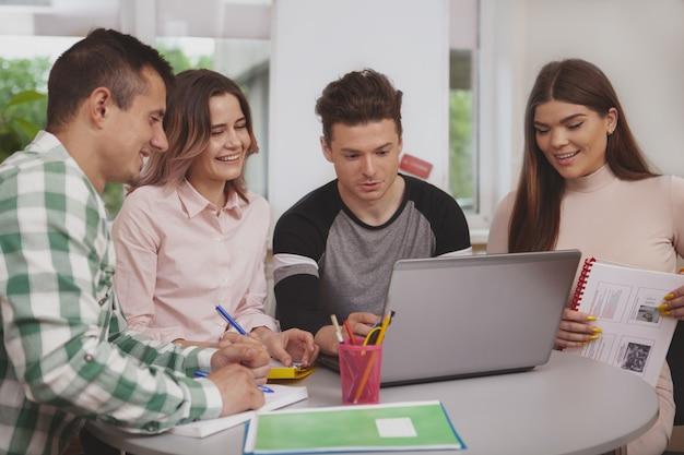 Grupo de jovens estudando juntos na sala de aula da faculdade