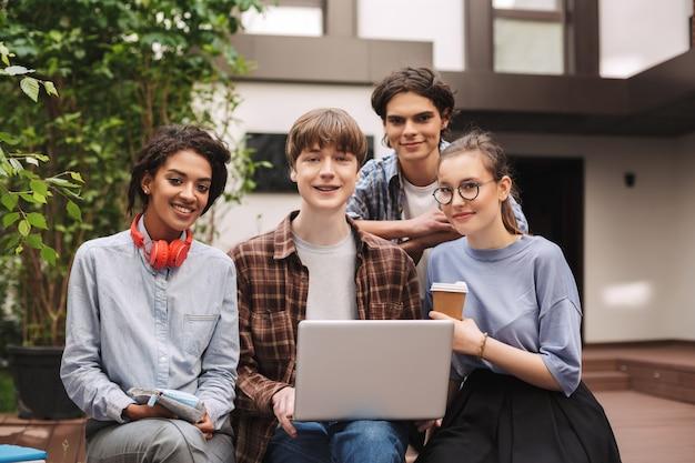 Grupo de jovens estudantes alegres, sentados no banco e trabalhando juntos no laptop, enquanto felizes