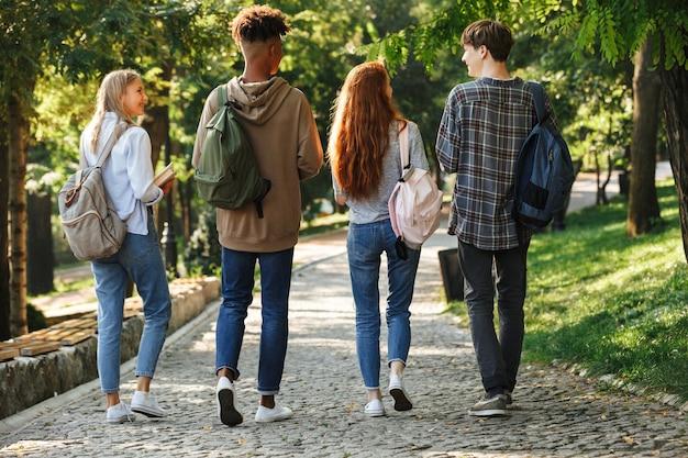 Grupo de jovens estudantes com mochilas nas costas