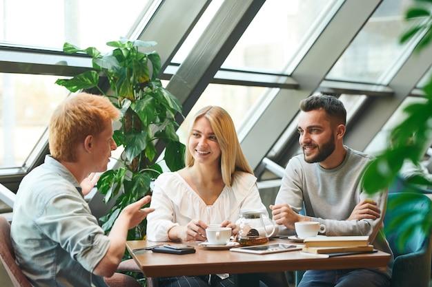 Grupo de jovens estudantes contemporâneos felizes reunidos à mesa no café após as aulas para um bate-papo e uma xícara de café ou chá